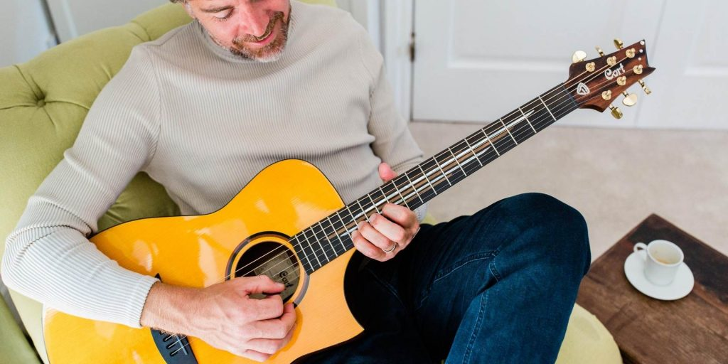 Man playing guitar - retiring at 40